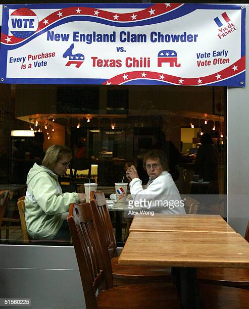 Two women are seen eating at a Vie de France restaurant as a banner which shows the choices of soups is hung above October 25 2004 in Washington DC...