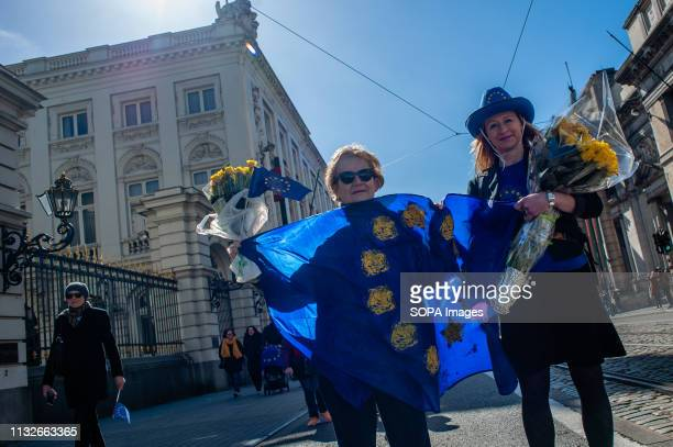 Two women are seen holding a flag of the EU and bouquets of yellow roses during the protest A day before the anniversary of the founding Treaty of...