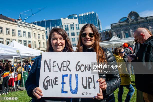 Two women are seen holding a placard that says Never gonna give EU up during the protest A day before the anniversary of the founding Treaty of the...