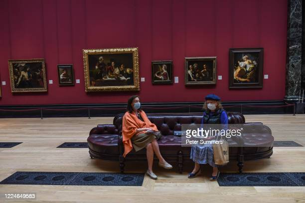 Two women are seen wearing masks while viewing paintings at the National Portrait Gallery during a press preview ahead of the gallery's reopening on...