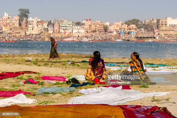 Two women are sitting on the sand banks at the holy river Ganges waiting for their laundry to dry panorama of Dashashwamedh Ghat Main Ghat in the...