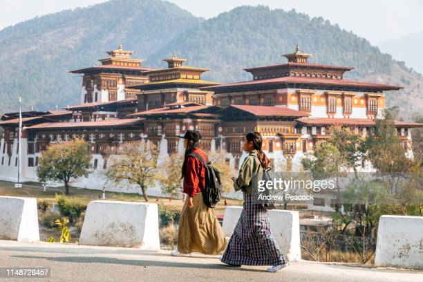 two women are walking past punakha dzong - bhutan stock pictures, royalty-free photos & images