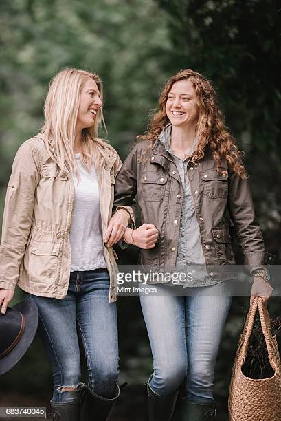 Two women arm in arm walking in coats and boots along a country path with a basket.