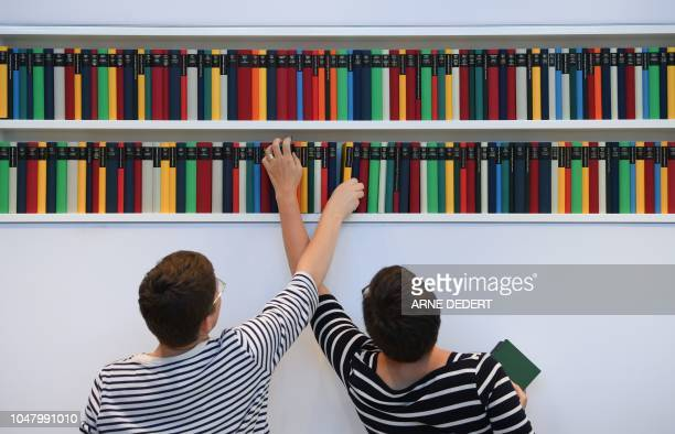 Two women arrange books in a shelf at the booth of the Diogenes publishing house as preparaatins are under way for the Frankfurt Book Fair on October...