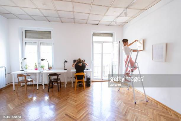 two women arranging office hub - positioning stock pictures, royalty-free photos & images