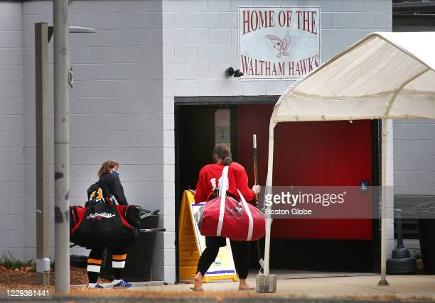 Two women arrive for a woman's hockey league game at the Veteran's Memorial Skating Rink in Waltham, MA on Oct. 23, 2020. The state will close all...