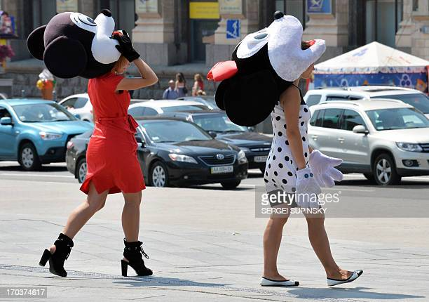Two women assistants of a street photographer wear masks of cartoon characters in spite of hot temperatures as they walk looking for clients in the...