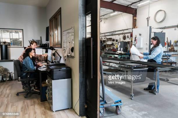 two women at a desk in office area of a metal workshop, woman standing at mobile workbench. - weibliche angestellte stock-fotos und bilder