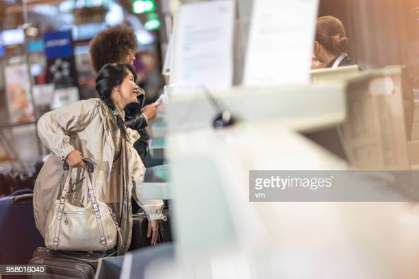 Two women at an airport check-in counter