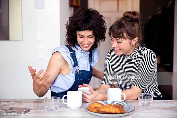 Two women at breakfast table looking together at smartphone