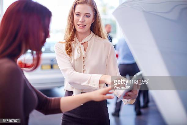 Two women at car dealer with digital tablet