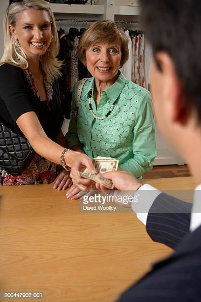 Two women at clothes store counter, one paying sales assistant