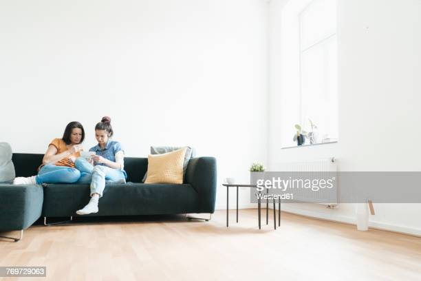 Two women at home sitting on couch looking at photos