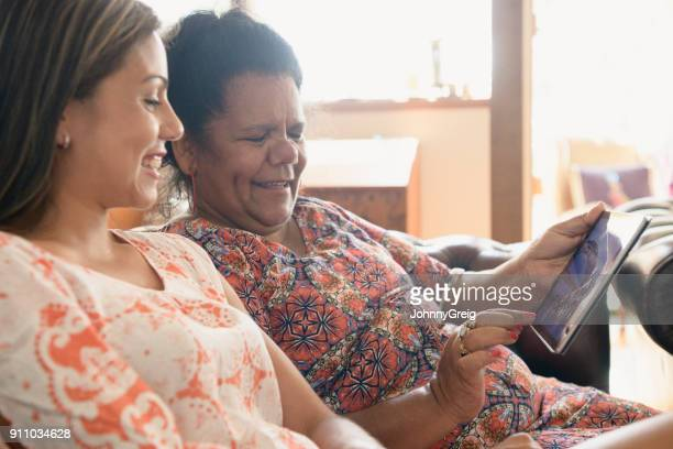 Two women at home using digital tablet