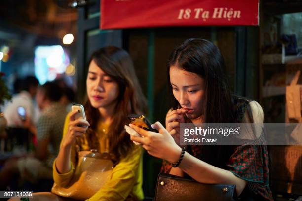 Two women at night sitting next to each other texting on their smartphones