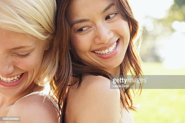 two women back to back, laughing and smiling - laura belli foto e immagini stock