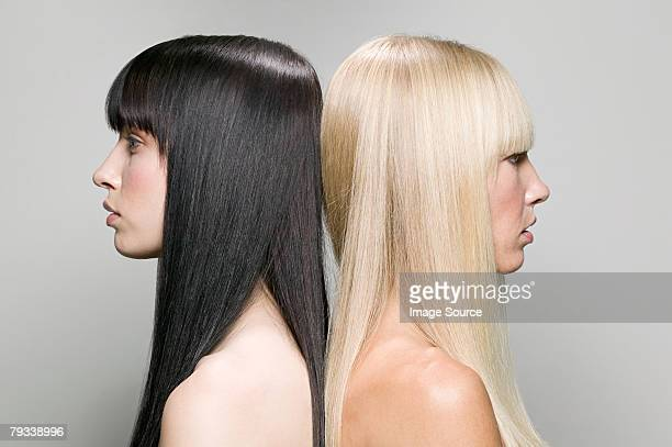 two women back to back - blonde hair stock pictures, royalty-free photos & images