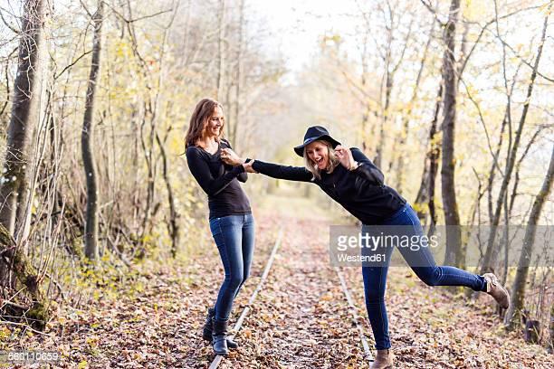 Two women balancing on rails