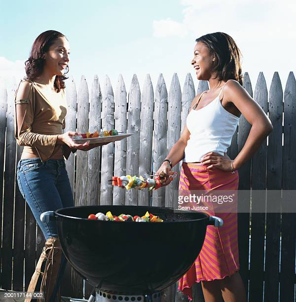 two women barbequing on roof deck - vegetable kebab stock pictures, royalty-free photos & images