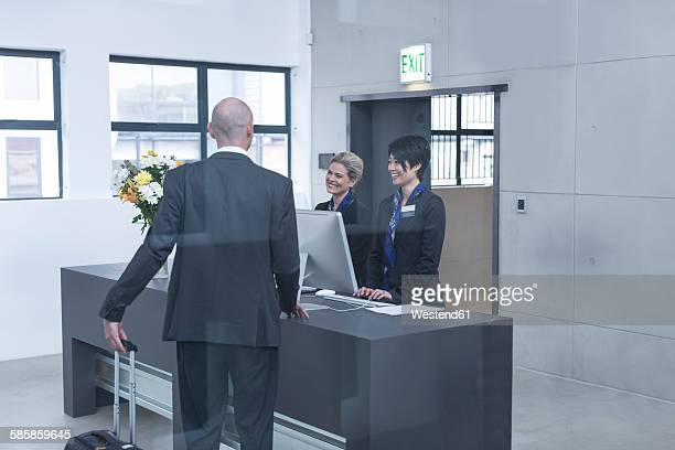 Two women behind reception desk in hotel lobby helping businessman