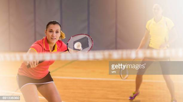 Two women behind the net playing badminton