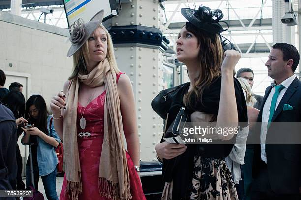 Two women - blonde and brunette wearing fascinators and summer dresses at Waterloo station, returning from a day at the Royal Ascot race meeting