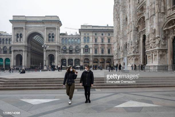 Two women both wearing a respiratory mask walk in Piazza del Duomo on February 25 2020 in Milan Italy Italy is the last country to be hit hard by the...