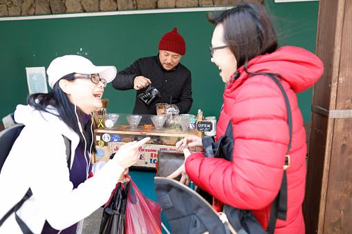Two women buying coffee - gettyimageskorea
