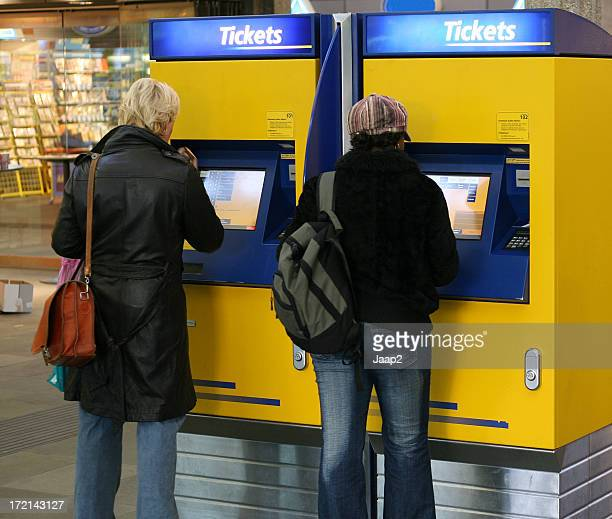 Two women buying train ticket at Dutch railway station
