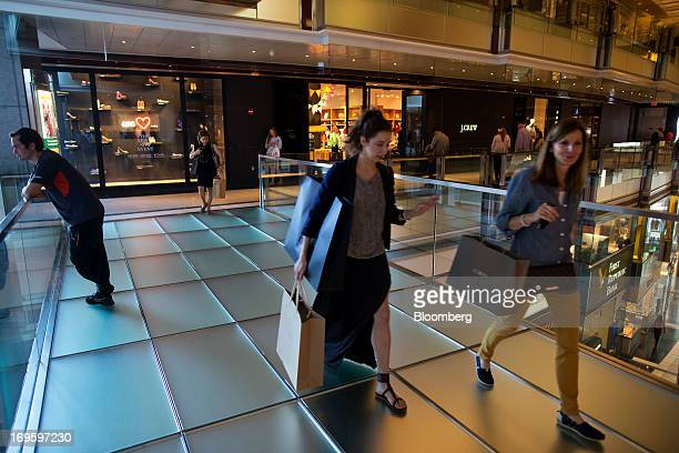Two women carry shopping bags while they walk through The Shops at Columbus Circle mall in New York US on Monday May 27 2013 Consumer confidence...