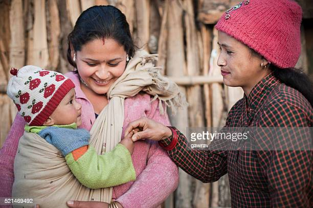Two women carrying and pampering a preschool child.