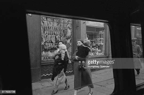 Two women carrying children on a street in Glasgow March 1939 Original publication Picture Post 91 Glasgow pub 1st April 1939
