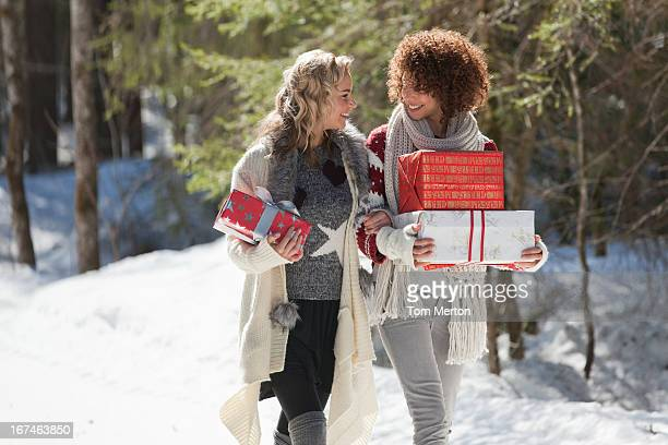 Two women carrying gifts outdoors in winter