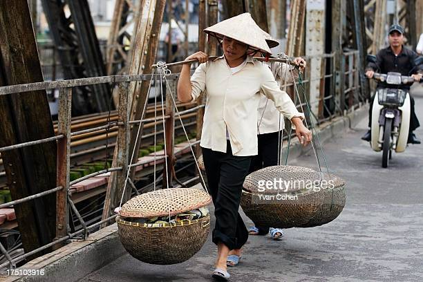 Two women carrying heavy loads walk across the Long Bien Bridge in Hanoi Hanoi is Vietnam's administrative capital and the seat of the nation's...