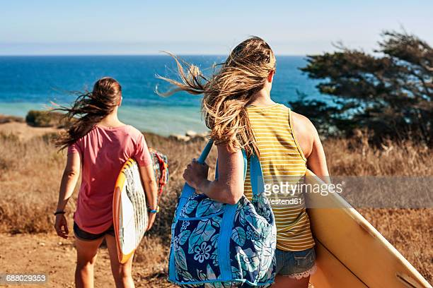 two women carrying surfboards at the coast - woman carrying tote bag stock photos and pictures