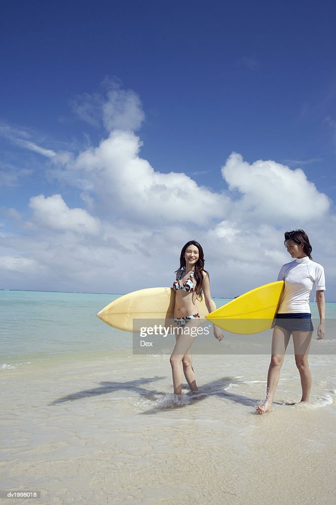 Two Women Carrying Surfboards on the Beach : Stock Photo