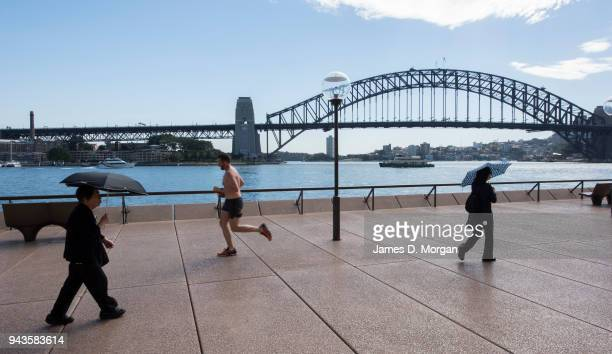 Two women carrying umbrellas for shade from the midday sun pass a lunchtime runner with the Harbour Bridge in the background on April 9 2018 in...