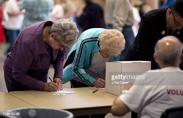 Two women casts their ballots for Republican candidates during the state's Republican caucus on March 5 2016 in Wichita Kansas People were standing...