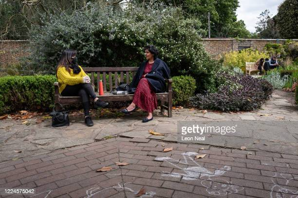 Two women chat as they sit on a bench in Golders Hill Park after aspects of the lockdown were eased on May 13 2020 in London England The prime...