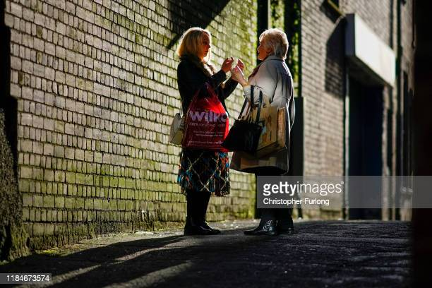Two women chat in an alleyway in Workington town centre after a political think tank declared that politicians need to win the vote of 'Workington...