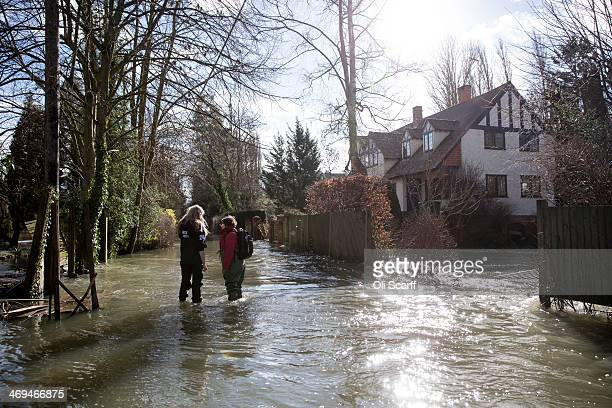 Two women chat on a flooded street adjacent to the river Thames on February 15 2014 in HenleyonThames EnglandThe Environment Agency continues to...