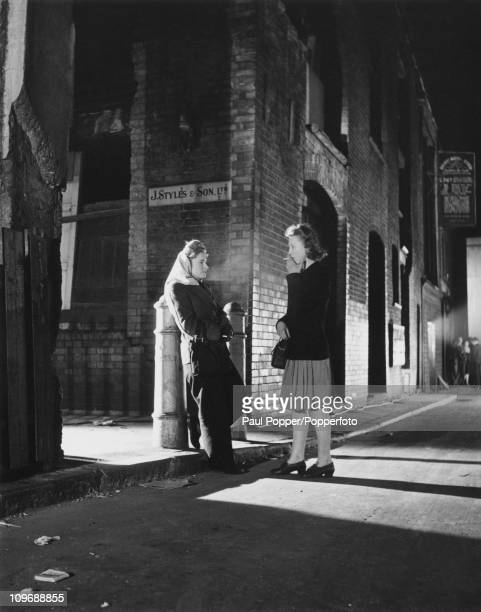 Two women chatting and smoking on a street in Soho London 1947