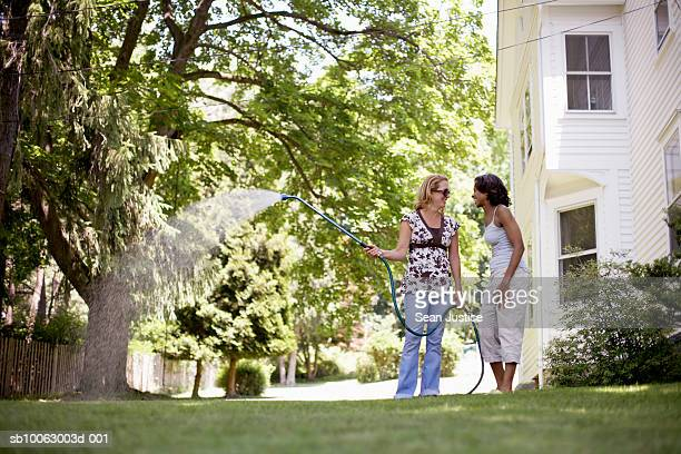 Two women chatting in house backyard, one watering lawn with hose