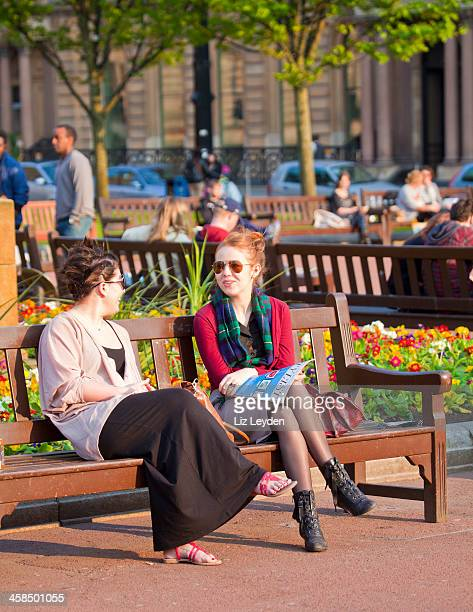 two women chatting on a bench in george square, glasgow - glasgow skottland bildbanksfoton och bilder