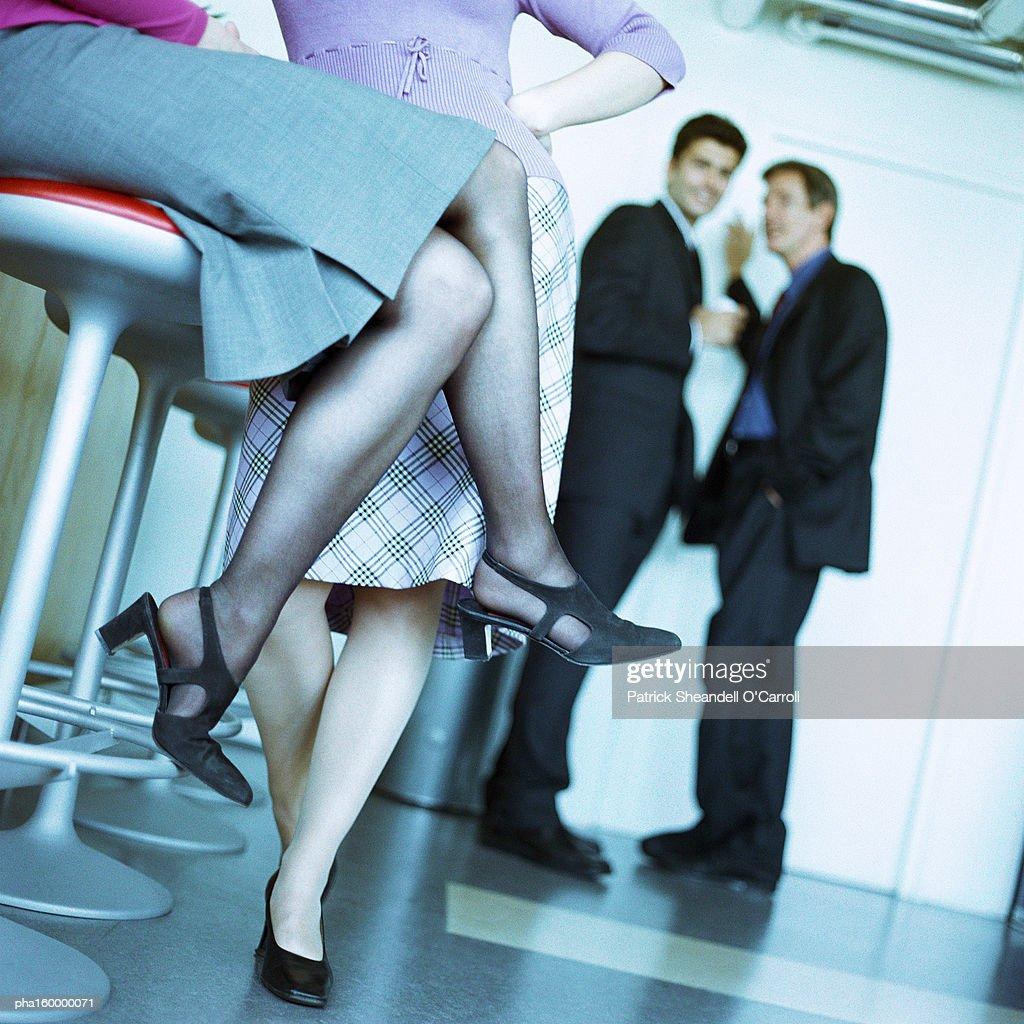 Two women chatting, two men in background, focus on women's legs. : Stockfoto