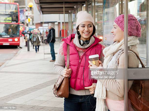 Two women chatting while waiting for bus.