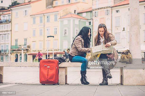 Two Women Checking the City Map, Sitting on a Bench