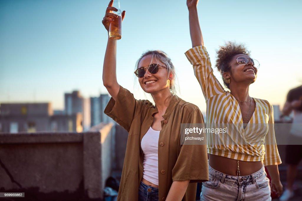 Zwei Frauen jubeln am Dach feiern. : Stock-Foto