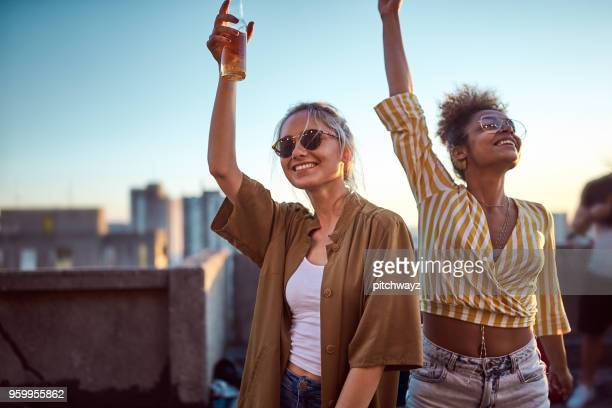 two women cheering at roof party. - after work stock pictures, royalty-free photos & images