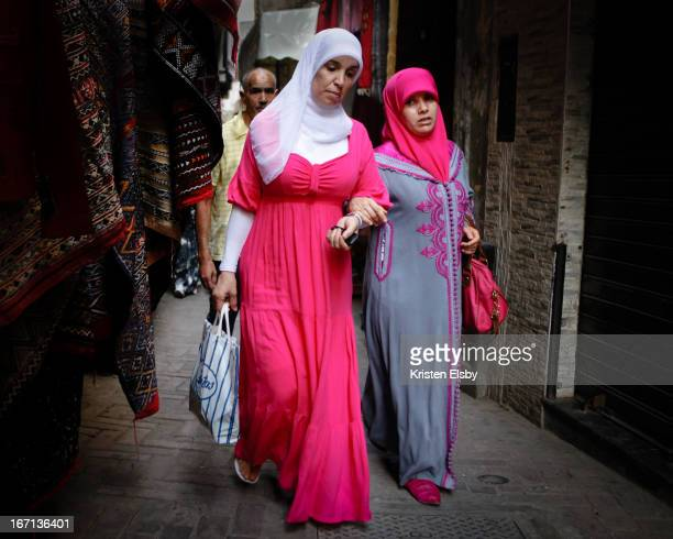 Two women clad in beautiful pink garments - the woman on the right wears a traditional, hand-embroidered djellaba with hand-made, pink leather...